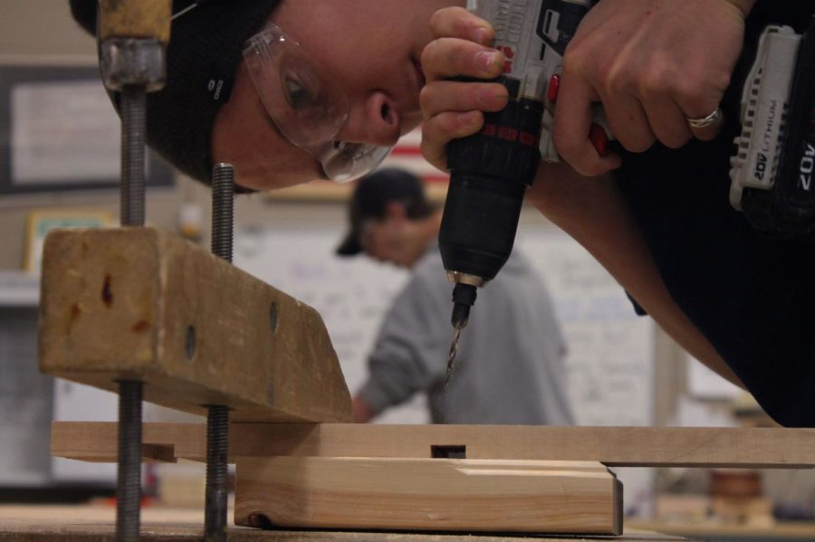 Jacob Cummins '23 uses the hand drill to cut holes in his wood to prep to put all his pieces together.