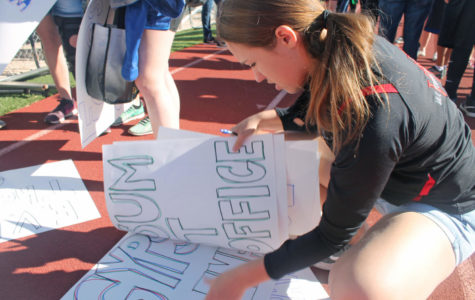 Community Service Day organizer Margaux Stavney '20 passes on signs for group leaders to hold to organize groups.