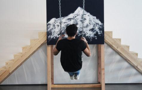 Adam Vasquez '19 swings on an interactive piece of art.